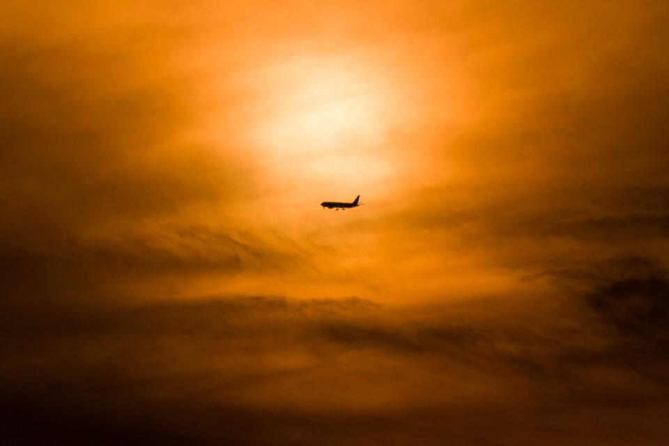 夕陽の空を飛ぶ飛行機